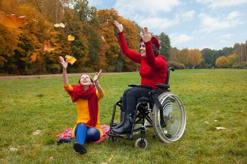 Donna in sedia a rotelle che si diverte con un'amica