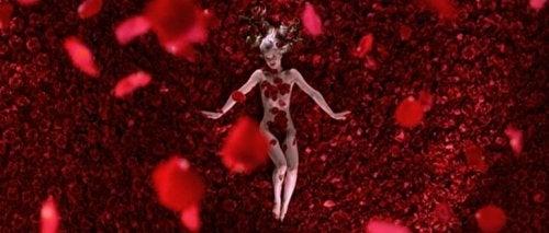 Scena del film American Beauty in cui si vede una donna nuda circondata da petali di rosa