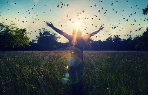 Donna in un campo con degli uccelli che volano