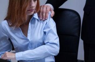 Mano di uomo sulla spalla di una donna discriminazione sessista