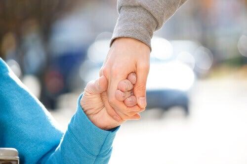 Persona disabile per mano a un'altra