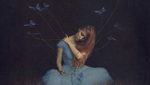 Ragazza le cui braccia sono legate a dei fili con delle farfalle