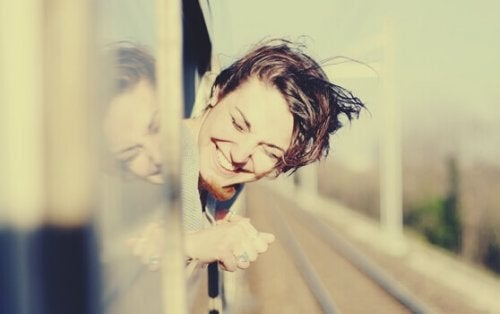 Ragazza sorridente affacciata al finestrino del treno