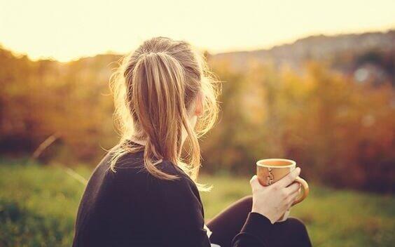Ragazza che beve una tazza di tè e stare bene
