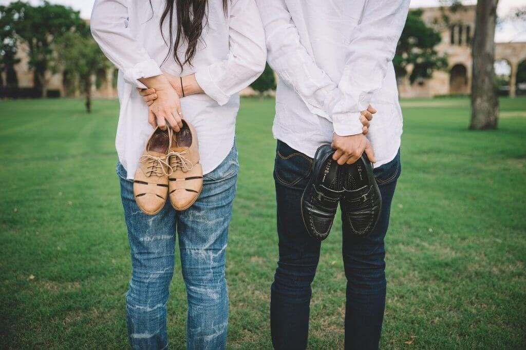 Uomo e donna in un campo con le scarpe in mano
