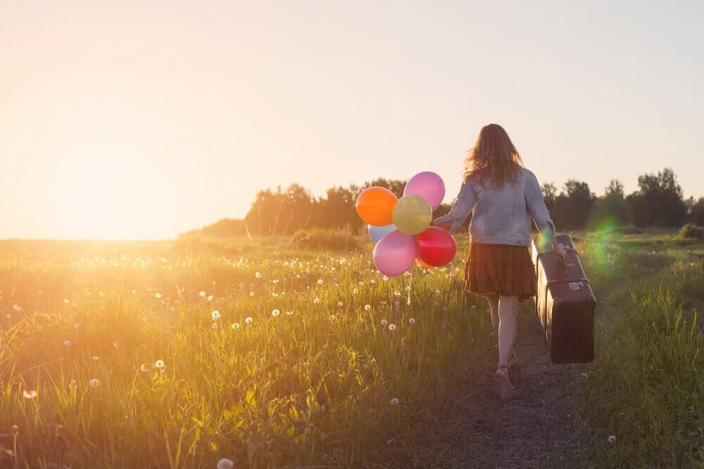 Ragazza con una valigia e dei palloncini in mano