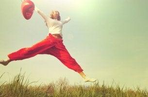 Ragazza che salta con un pallone rosso