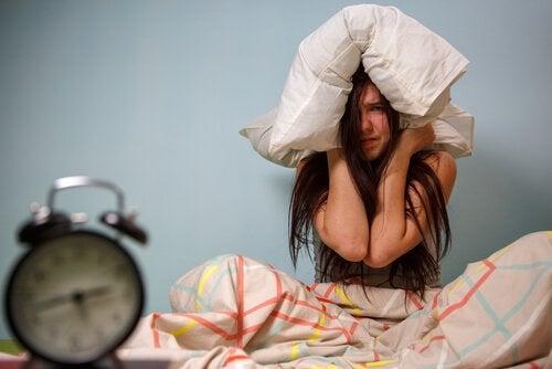 Adolescente con cuscino in testa e sveglia