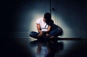 Adolescente seduto nell'oscurità