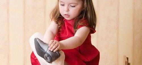 Una bambina che si mette le scarpe