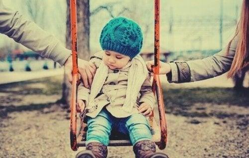 Bambino su altalena con genitori ai lati