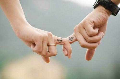 Coppia con tatuaggio che si tiene per mano