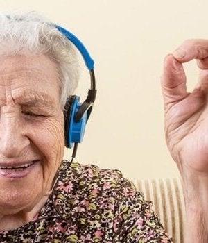 Donna affetta da Alzheimer che ascolta musica