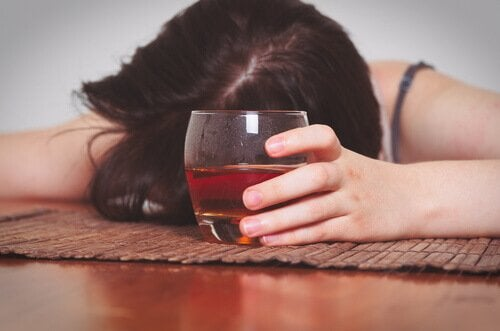 Donna ubriaca bere per dimenticare