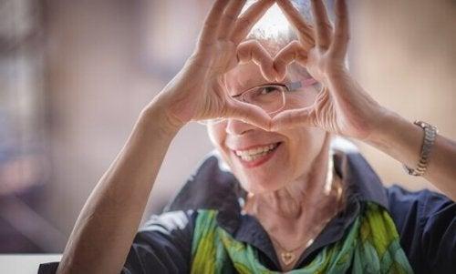 Donna anziana felice che fa cuore con le mani invecchiare in modo sano
