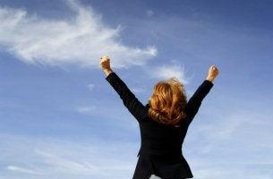 Donna che esulta alzando mani al cielo gestire il fallimento