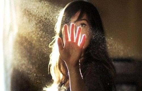 Donna che mette la mano in un fascio di luce