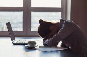 Una donna con la testa in giù sul tavolo persone dipendenti dalla negatività
