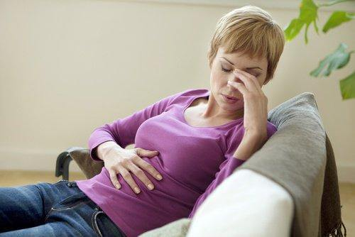 Donna con dolore di stomaco dovuto al Lexotan