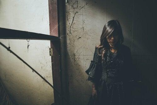 Donna vestita di nero appoggiata al muro
