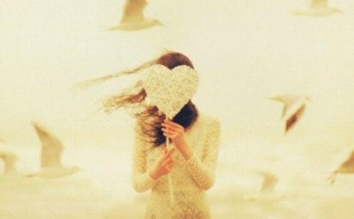 Ragazza che si copre il volto con un cuore