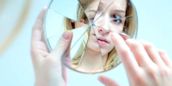 Ragazza che si guarda in uno specchio rotto essere troppo autocritici