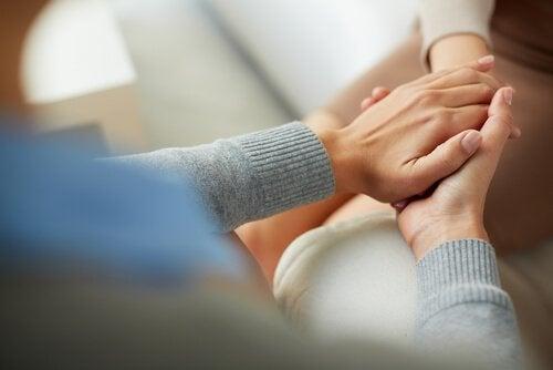 Terapeuta che tiene le mani del paziente counseling