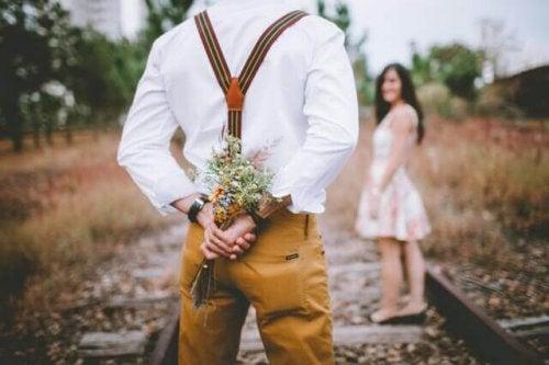 Uomo ad appuntamento con ragazza con fiori dietro la schiena