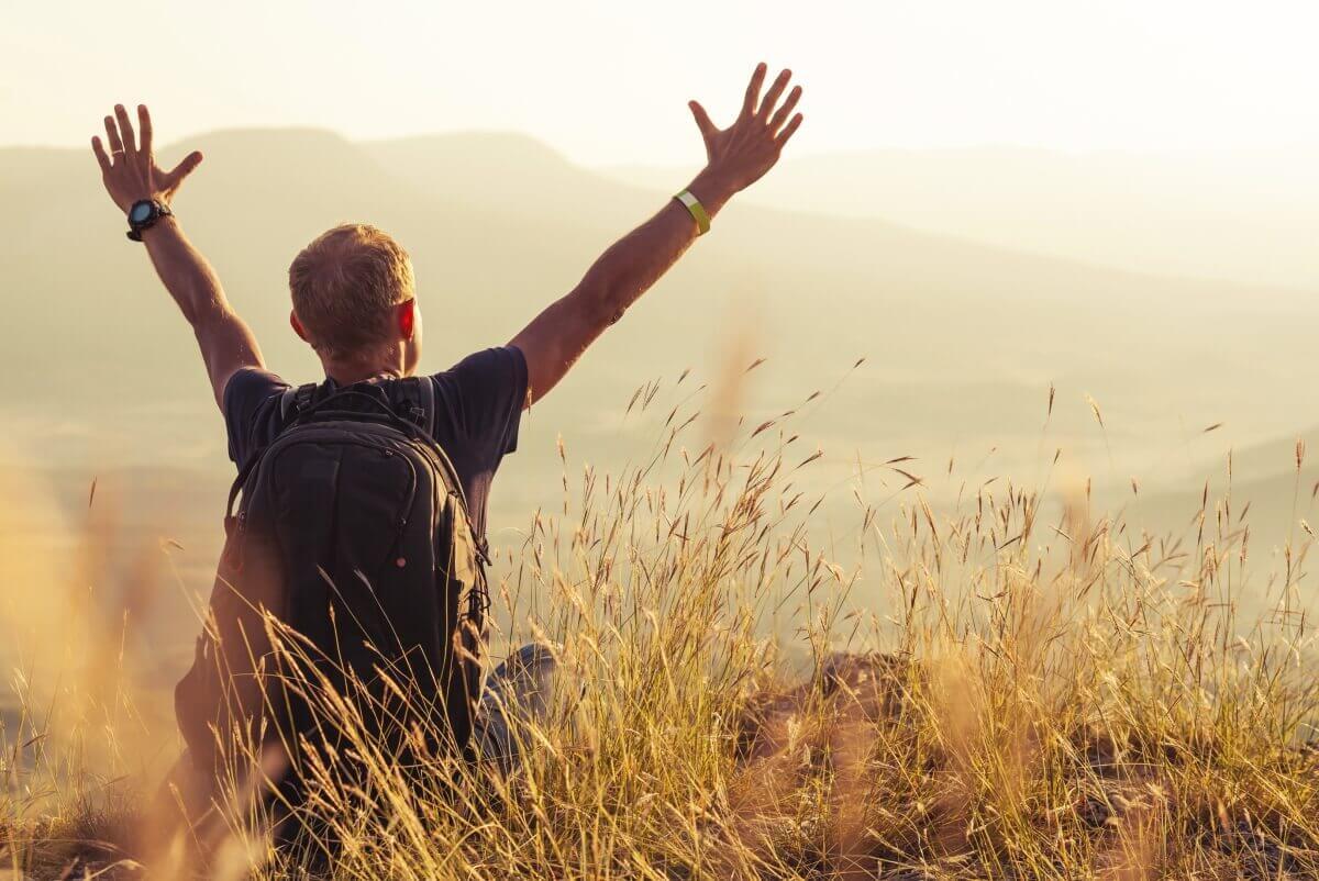 Uomo nella natura con le braccia alzate