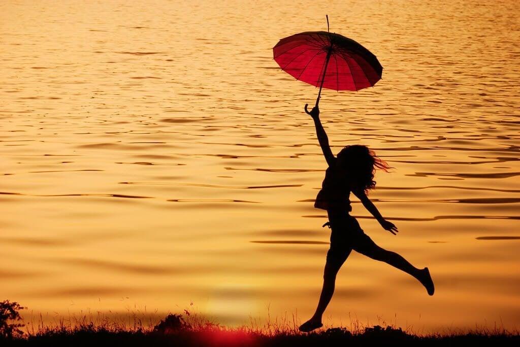 Donna in riva al mare con un ombrello
