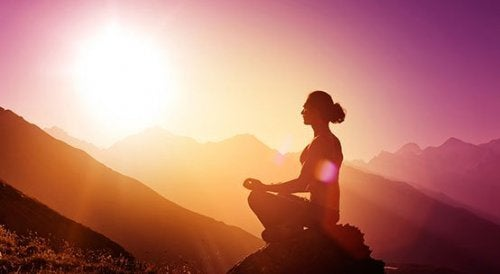 Dona che medita sulla montagna