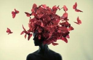 Donna con delle farfalle rosse sulla testa pensare positivo