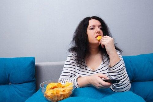 Una donna che mangia patate la sedentarietà