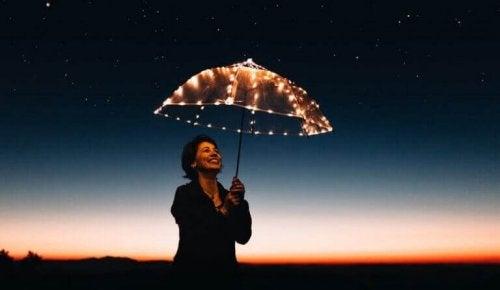 Donna con un ombrello illuminato da luci
