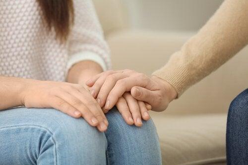 Mano psicologo sulla mano della paziente