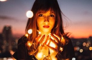 Ragazza che tiene in mano delle luci, simbolo della paura di brillare