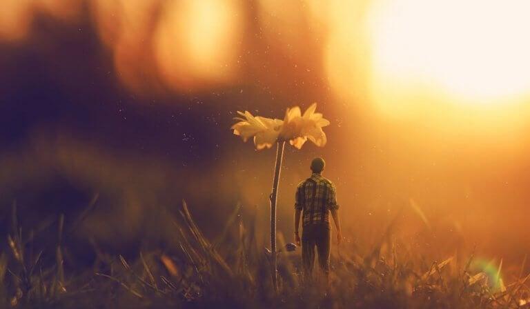 Uomo in miniatura sotto un fiore