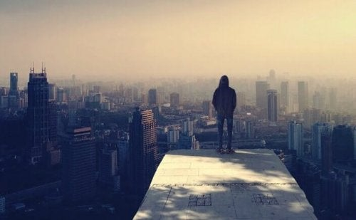 Ragazzo in cima a dei grattacieli che pensa alla paura di brillare