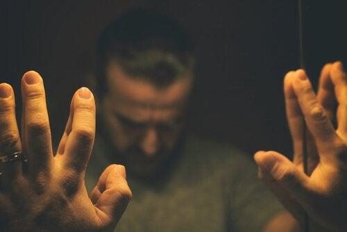 Uomo con mani sullo specchio