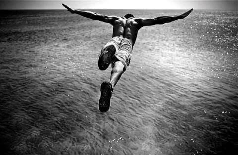 Uomo che si tuffa nel mare da uno scoglio, per sentire l'adrenalina