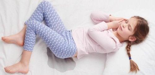 Bambina che dorme su letto bagnato