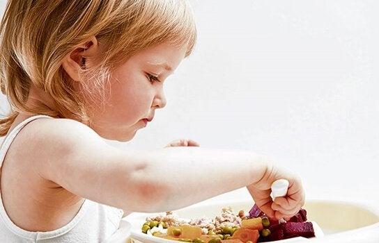Bambina che mangia verdure