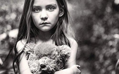Bambina che stringe un orsetto e rappresenta il dolore cronico infantile