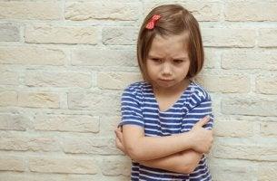 Bambina triste a causa del ricatto emotivo dei genitori