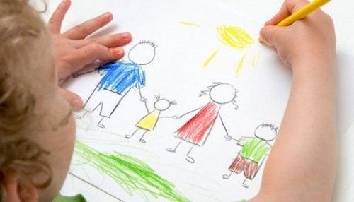 Bambino che disegna la sua famiglia