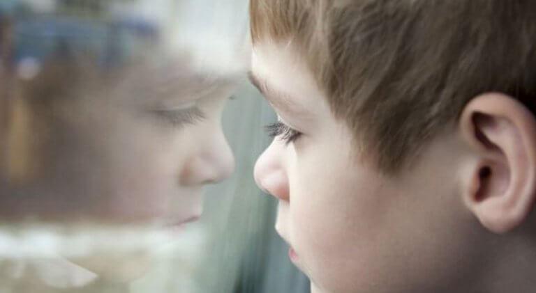 Bambino triste che guarda dalla finestra