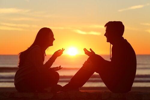 Coppia in spiaggia al tramonto che parla