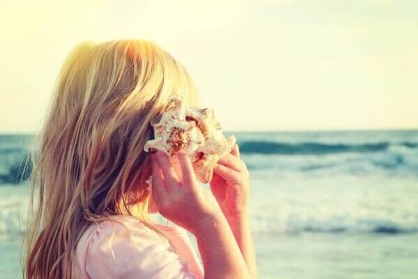 Donna che ascolta il rumore del mare nella conchiglia
