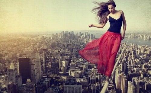 Donna che cammina su corda sopra alla città