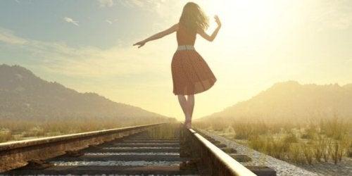 Donna che cammina sui binari